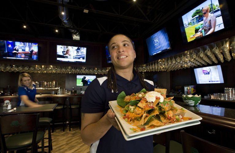 Jasmine Curtis, kitchen manager of the new Green Turtle sports bar in Kernstown Commons, holds a plate of buffalo nachos inside the new establishment located beside the Alamo Drafthouse Cinema. The sports bar will open for business at 11 a.m. Monday. Rich Cooley/Daily